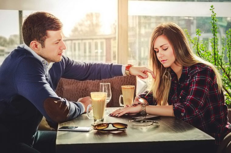 Man and woman sitting at a restaurant table talking.