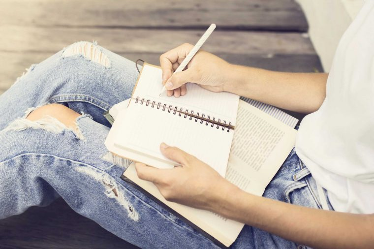 Woman in torn jeans writing in a journal with a pen.