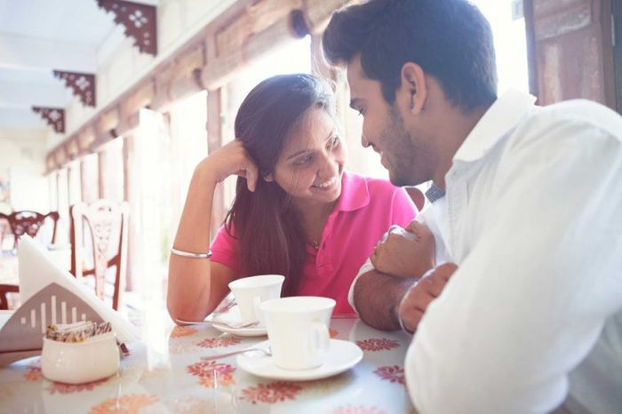 A man and woman sitting in a cafe talking and smiling.