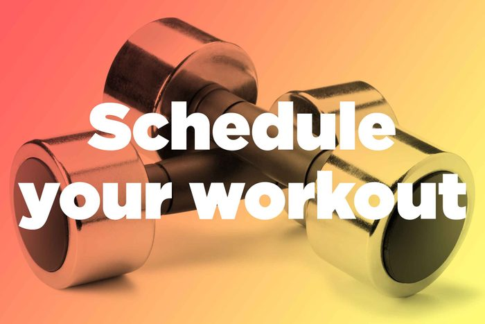 """Words """"schedule your workout"""" over hand weights"""