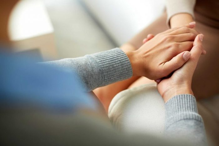 A woman holding a person's hand in both of her hands.