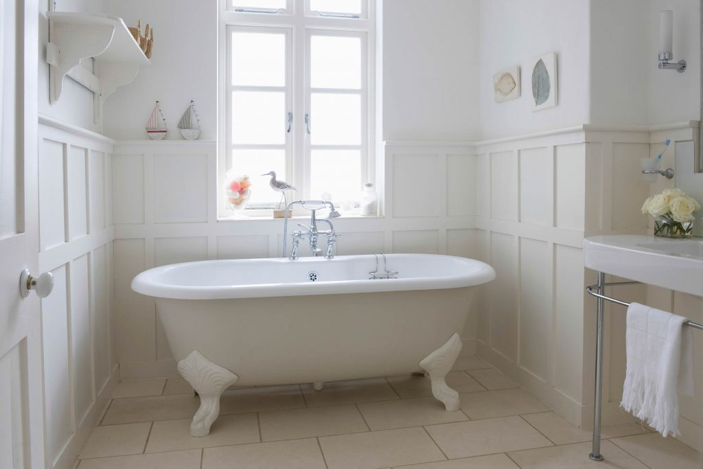 white clawfoot tub in a white sunny bathroom