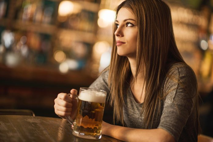Woman in bar drinking beer alone