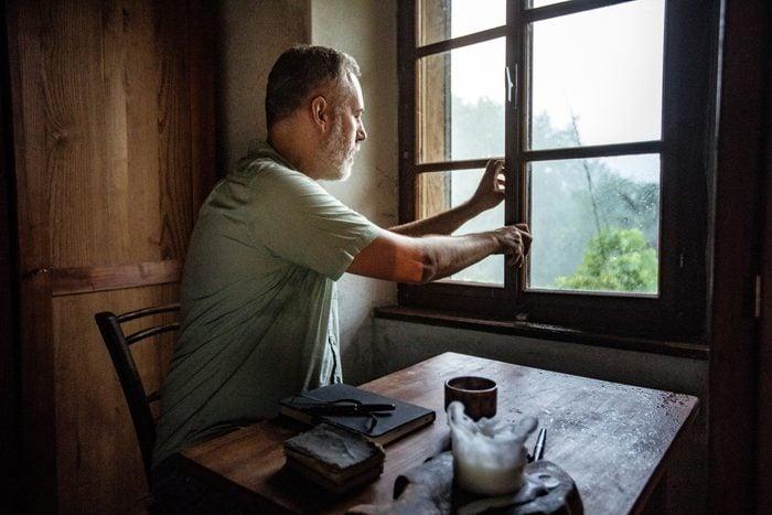 man closing window in home