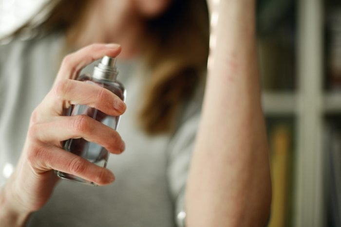 close up of woman spraying perfume on arm