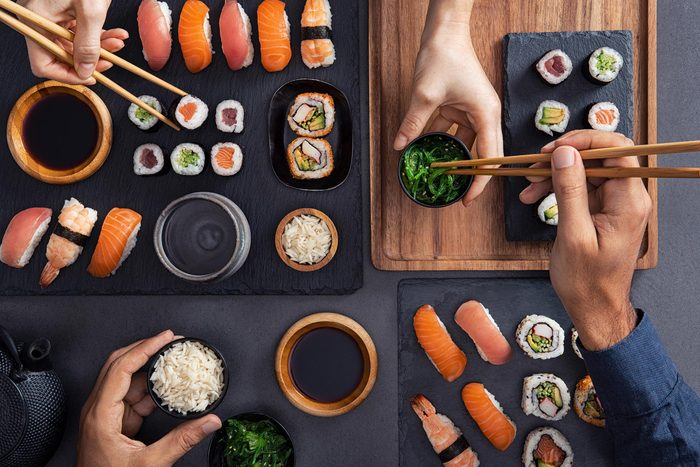 People eating sushi at a restaurant.