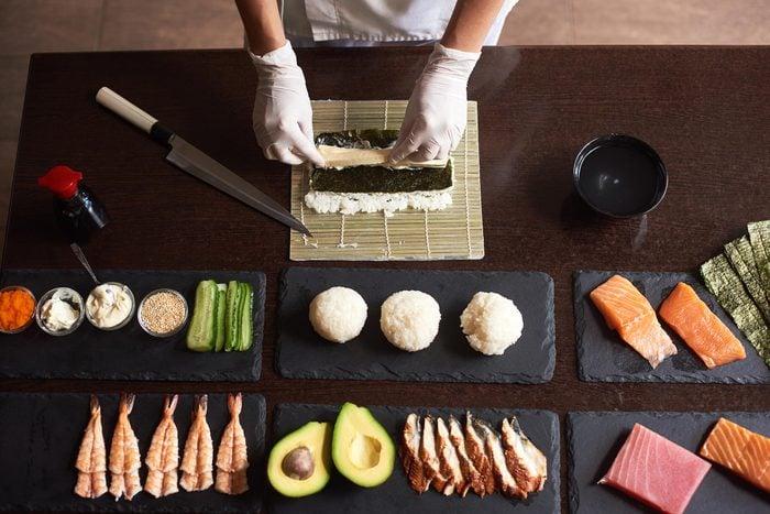 Sushi chef making sushi rolls.