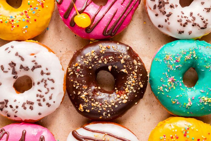 colorfully decorated doughnuts topped with sprinkles and drizzles