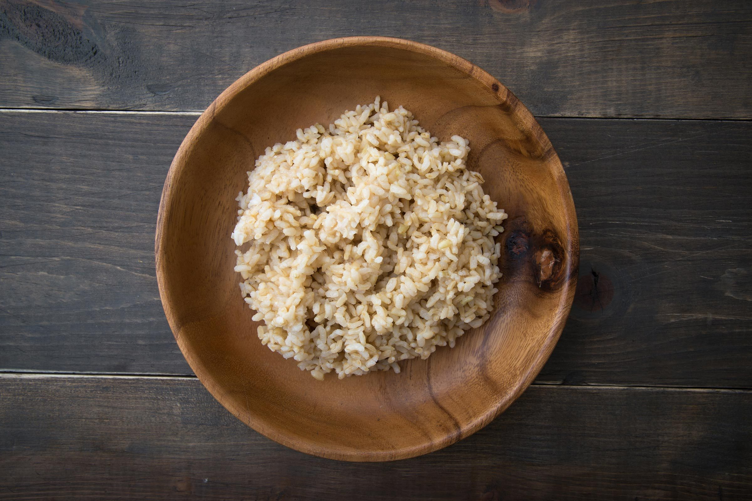 Wooden bowl of brown rice.