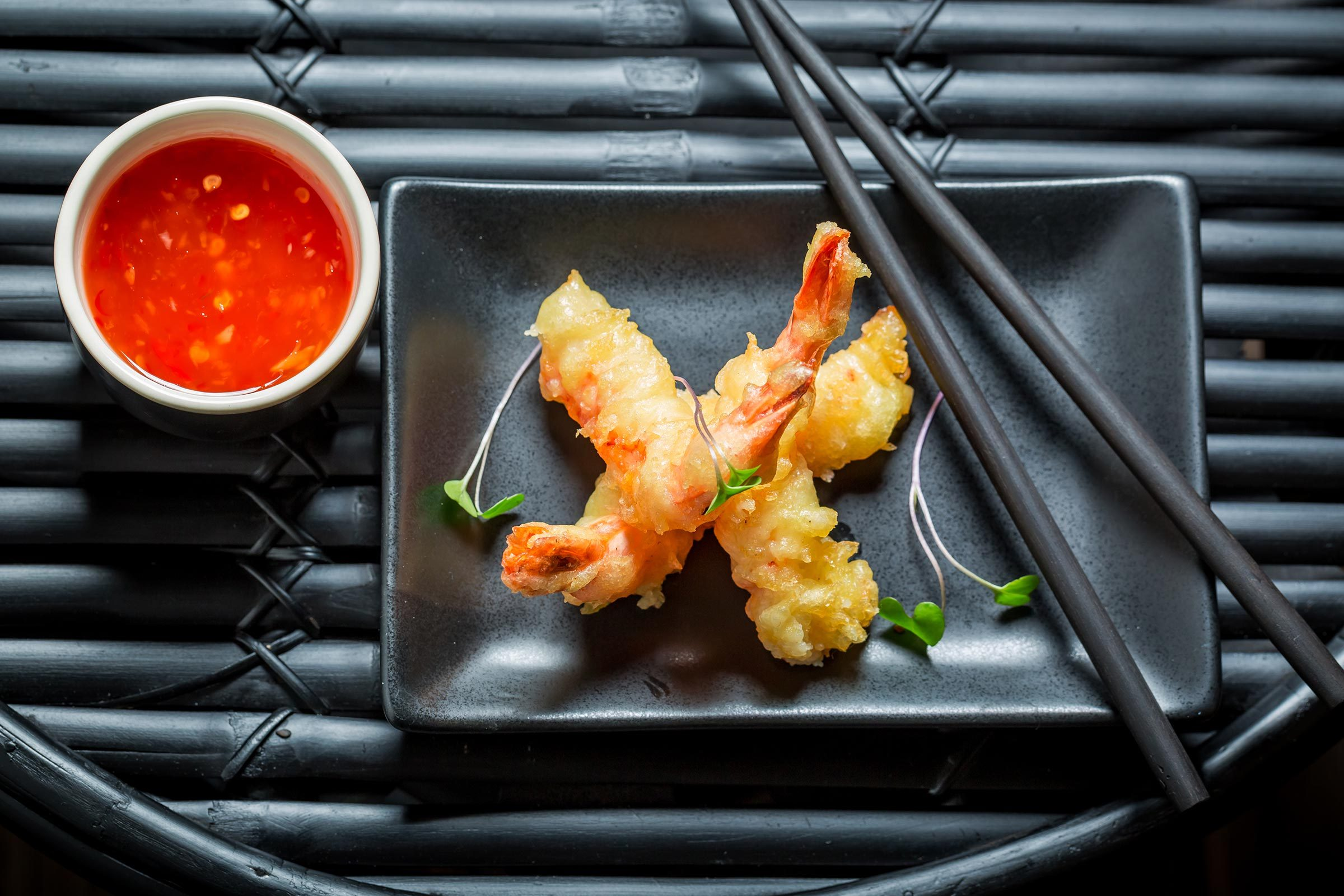 Fried shrimp tempura on a black plate.