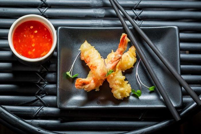 Fried shrimp tempura on a black plate.