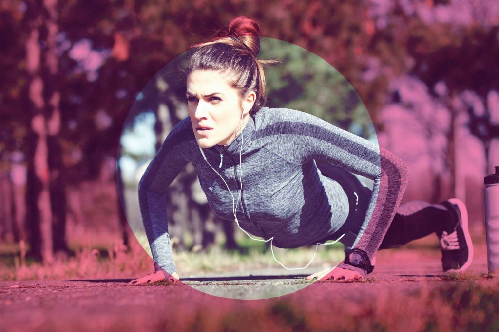 woman with earbuds outdoors doing pushups