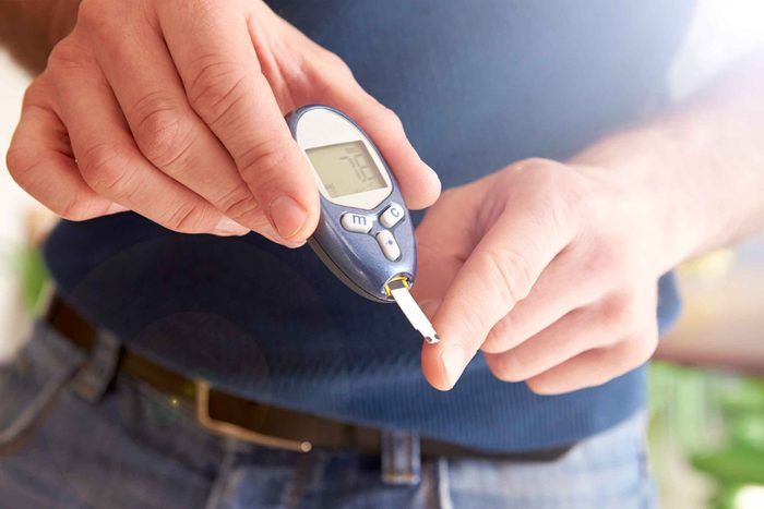 man checking his blood sugar with a device