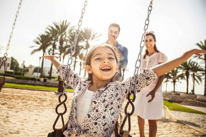 Little girl sitting on a swing in a park with her parents in the background.