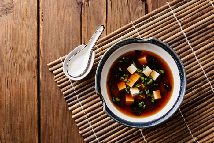 Bowl of miso soup on a mat.