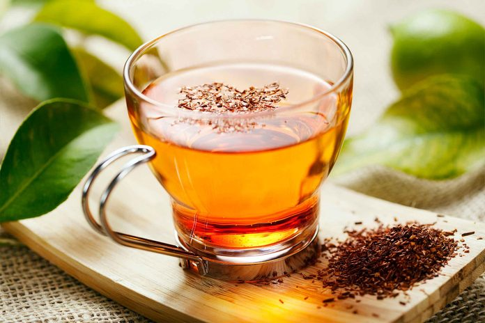 glass mug of tea next to pile of dried tea