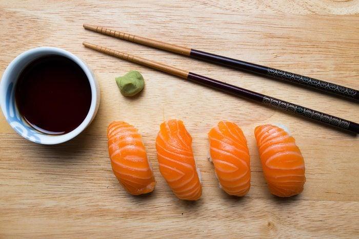 Four pieces of salmon sashimi and soy sauce.