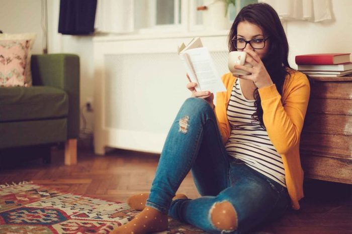 Woman sitting on the living room floor reading a book and drinking from a mug.