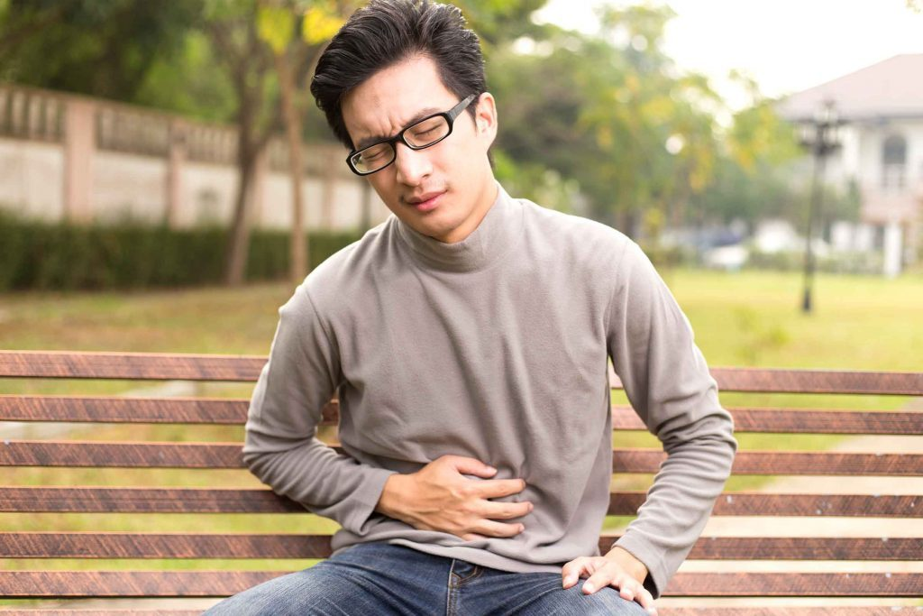 man sitting on a park bench holding his stomach and wincing