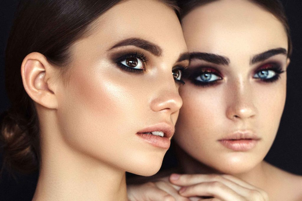 two dark-haired women with lots of eye makeup