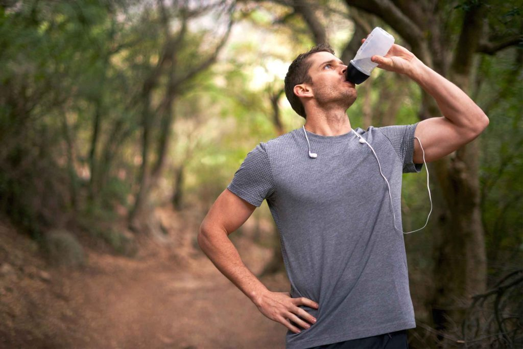 man on a trail drinking from water bottle