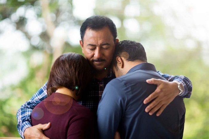 Man hugging two people outdoors.