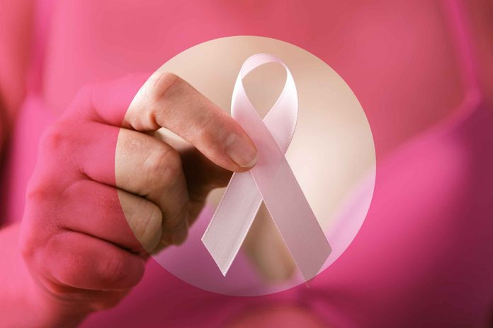 closeup of a hand holding a pink breast cancer ribbon
