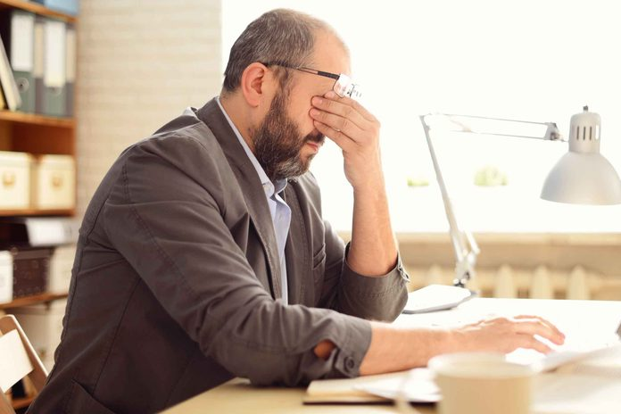 man sitting at a desk in an office rubbing his eyes