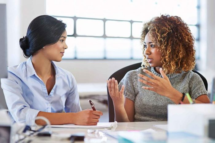 Two women office workers speaking to each other at a table.