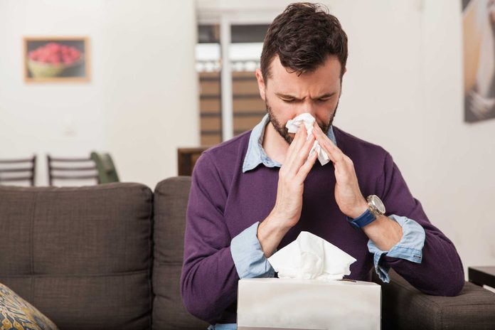 Man sitting on a couch blowing his nose with a tissue.