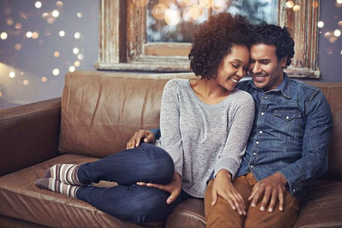 Man and woman sitting on a brown leather couch together.