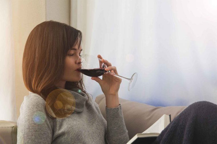 Woman reading a book on the couch drinking red wine.