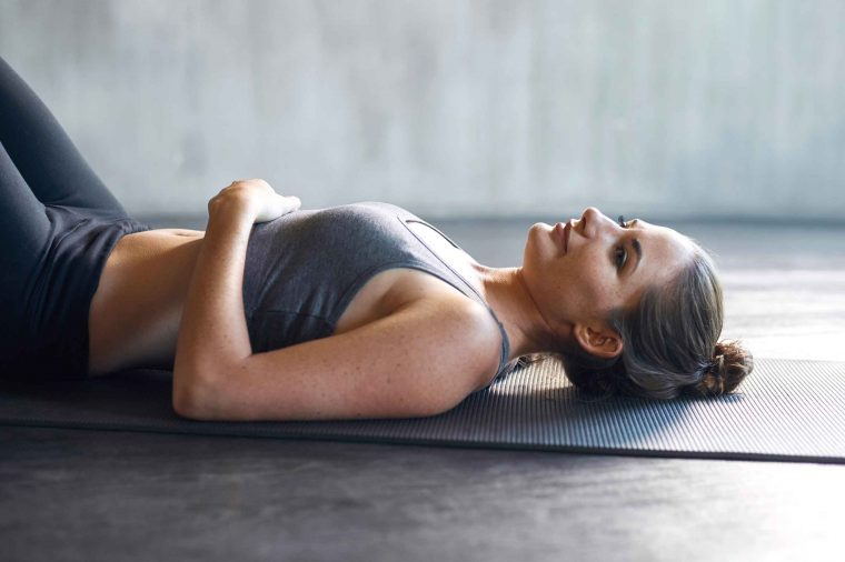 Woman in workout clothes lying on a yoga mat at the gym.