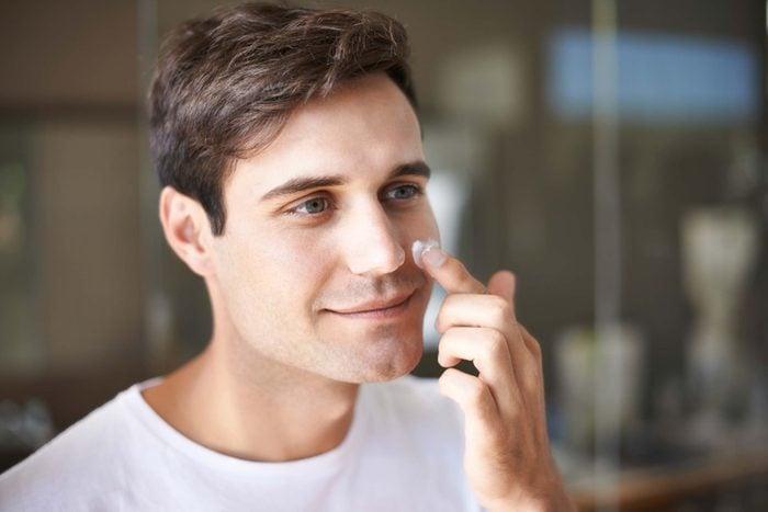 man dabbing sunscreen on cheek