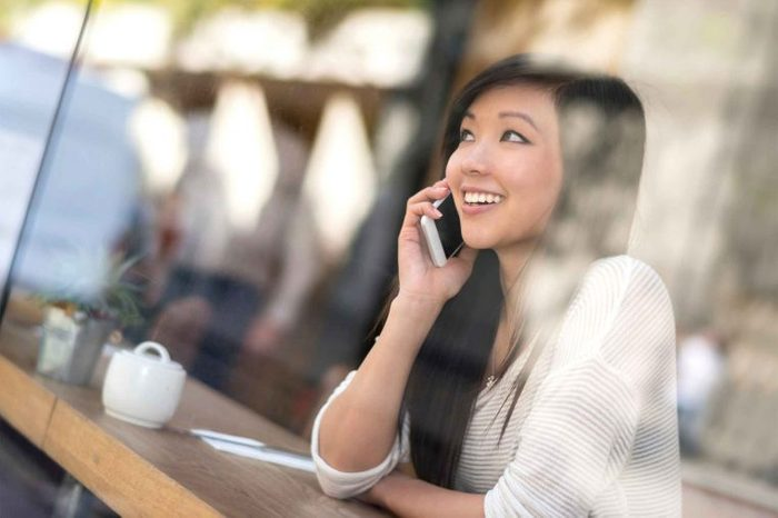 Woman sitting in a coffee shop smiling and talking on her phone.
