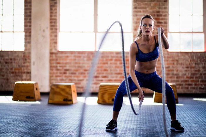 Woman doing rope wave exercises at a gym.