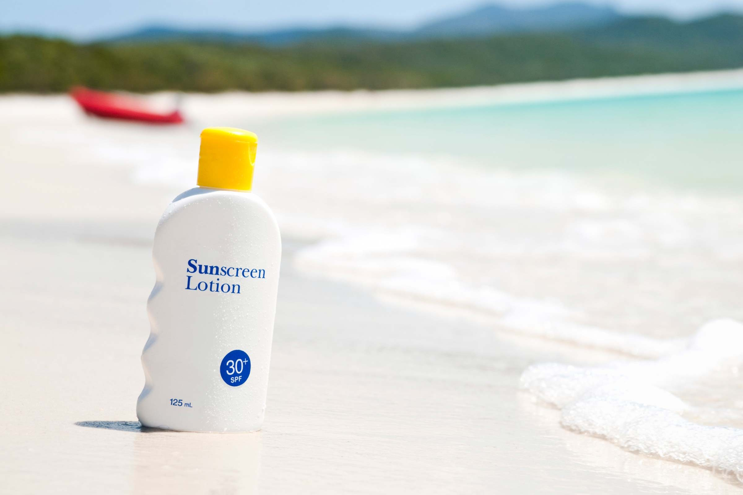 bottle of sunscreen in the sand