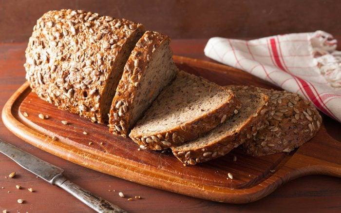 half-sliced broad bread on wooden board