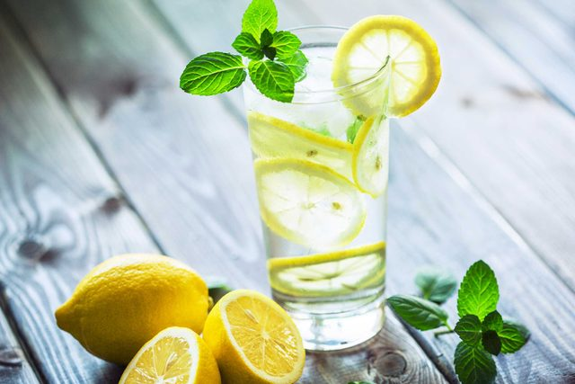 glass of water with lemon slices and mint