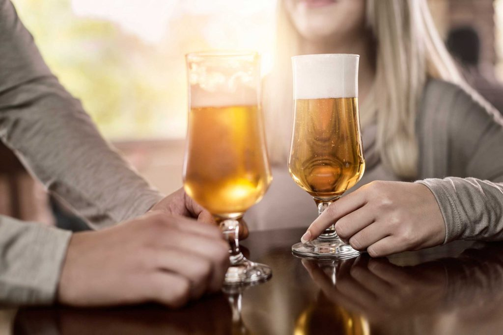 Man and woman drinking craft beer at a bar.
