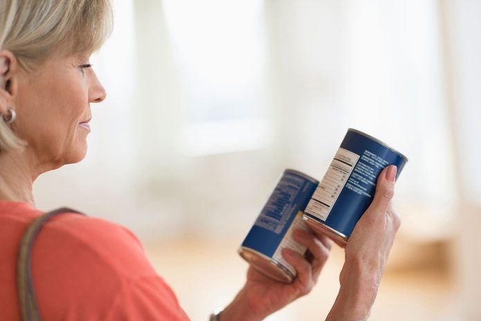 woman reading nutrition label on two cans of food