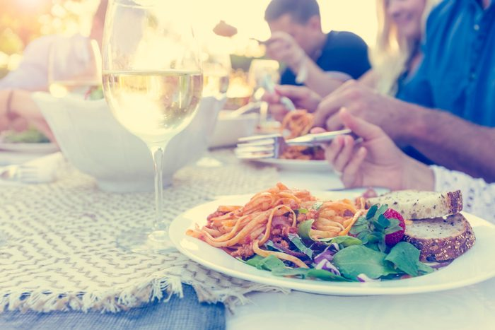 people eating salad with bread and glass of wine
