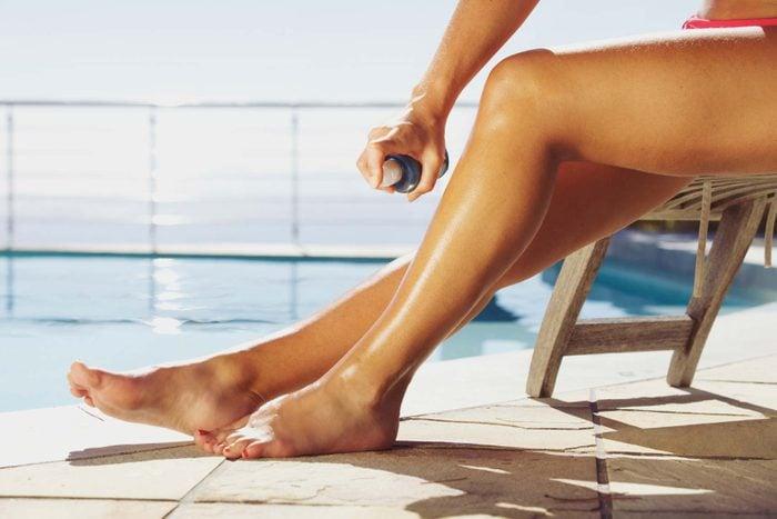 spraying sunscreen on legs at pool