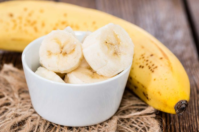 bowl with banana slices in front of ripe banana