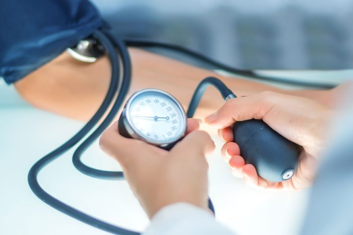 doctor measuring blood pressure on patient's arm