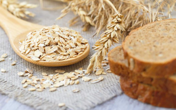 stalks of wheat, wheat kernels on a spoon, slices of brown bread