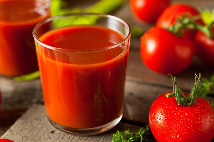 glasses of tomato juice surrounded by fresh tomatoes