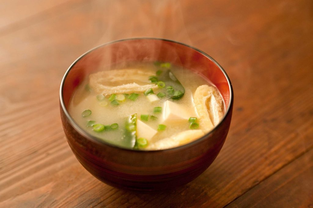 bowl of steaming miso soup with green onion and tofu