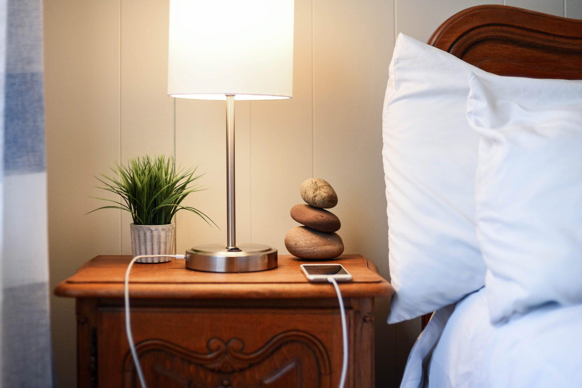 smarphone charging on nightstand next to bed