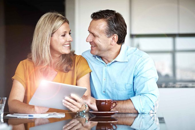 couple smiling over coffee and documents